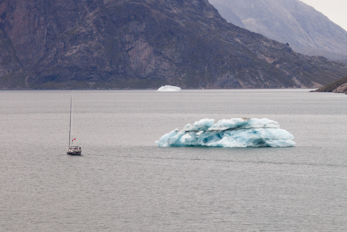 A sailing boat rounding an iceberg.
